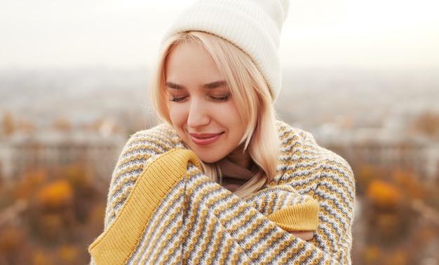 Молодая женщина, завернувшись в одеяло в сельской местности