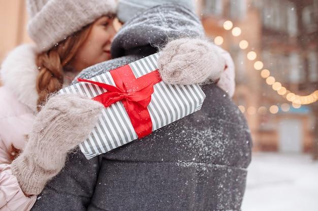 젊은 여자는 외부 겨울 공원에서 발렌타인 데이 휴가 선물로 인해 행복 해지는 그녀의 남자 친구 목 주위에 그녀의 손을 감싸고 있습니다. 사랑, 행복, 공생 및 데이트 개념.