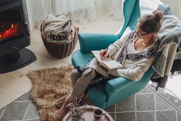 若い女性は暖炉のそばの居心地の良いアームチェアに座ってノートに書き込みます