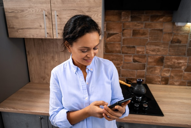 The young woman writes a message on the smartphone while standing in the kitchen.
