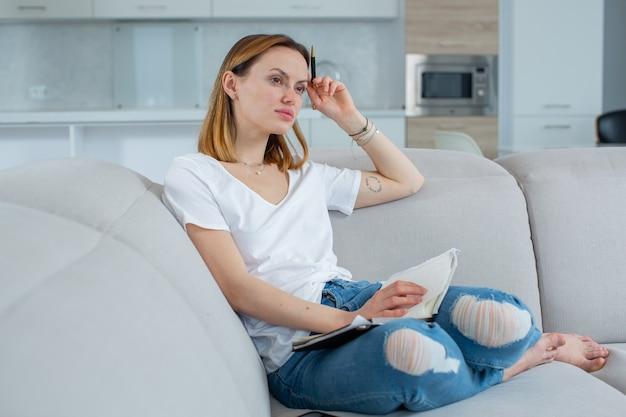 젊은 여성은 집에서 베이지색 소파 고품질 사진에 앉아 공책에 시를 씁니다.