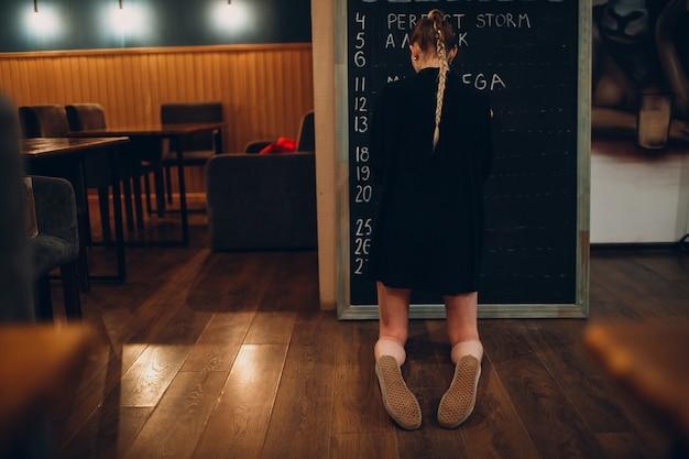 Young woman writing cafe menu on black desk chalkboard using chalk.