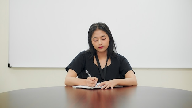 Young woman writing her homework on the table