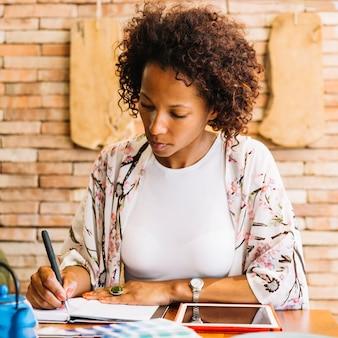 Молодая женщина, писать в дневник с ручкой и цифровой планшет на деревянный стол