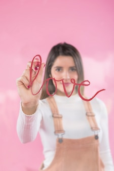 Young woman writing love on glass with lipstick