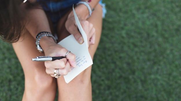 Молодая женщина, писать сообщение на бумаге с ручкой