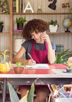Молодая женщина что-то пишет в своей тетради в теплице