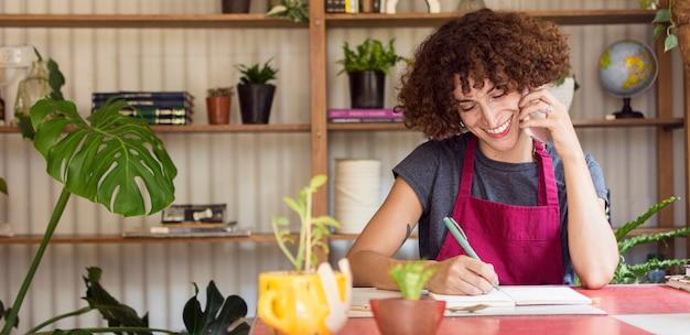 Молодая женщина, что-то писать в своей записной книжке с копией пространства