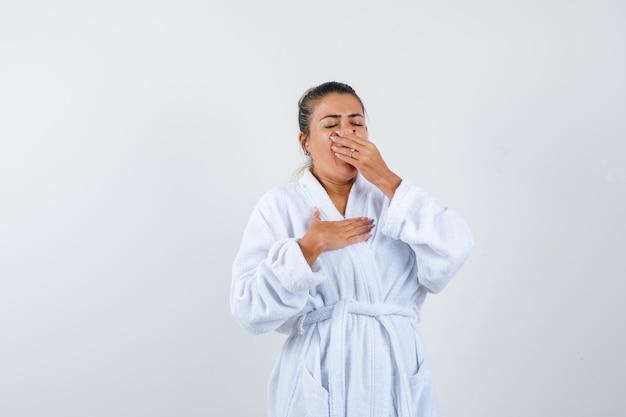 バスローブであくびをして眠そうな若い女性