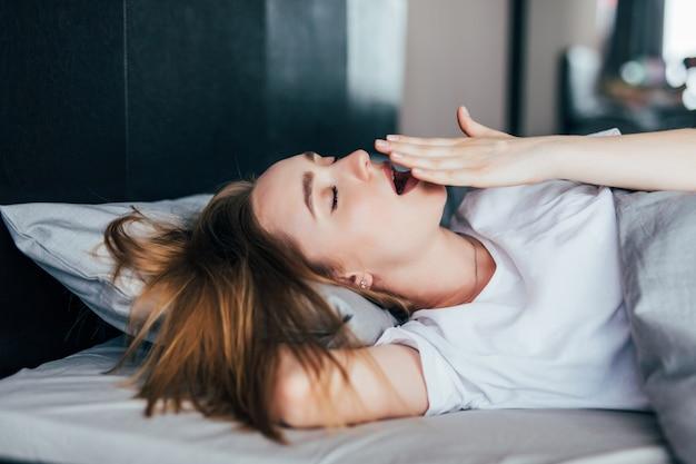 Молодая женщина, зевая в постели у себя дома