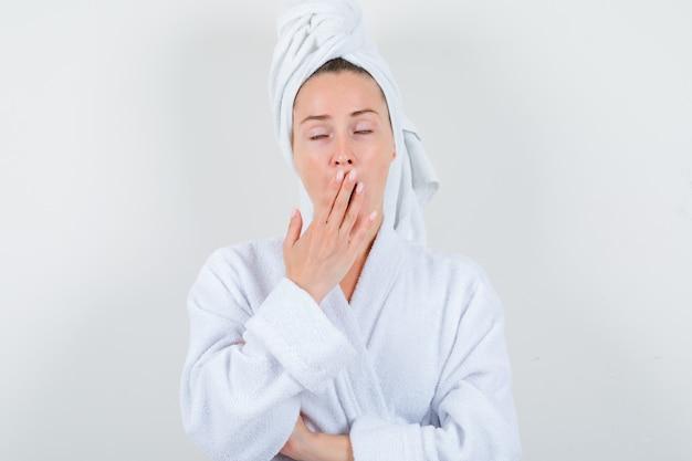 白いバスローブ、タオルであくびをし、眠そうな顔をしている若い女性、正面図。