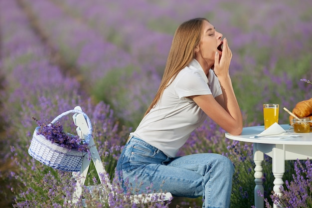 Young woman yawning in lavender field