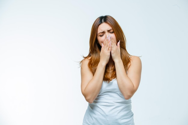 Giovane donna che sbadiglia con le mani sulla bocca