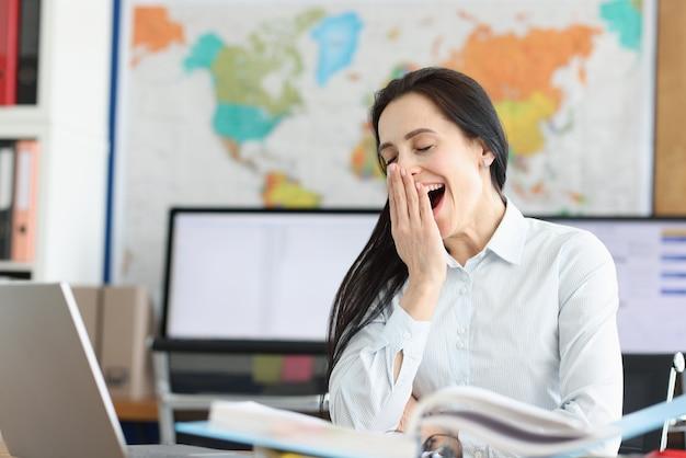 Молодая женщина зевает на рабочем месте для ноутбука