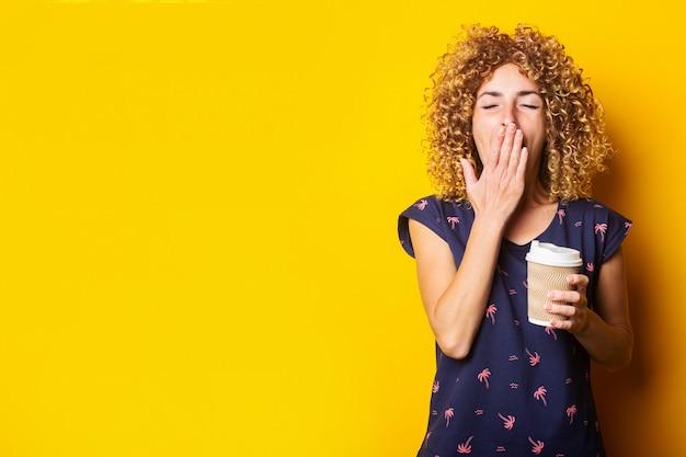 Молодая женщина зевает, прикрывает рот рукой, держащей бумажный стаканчик на желтой поверхности