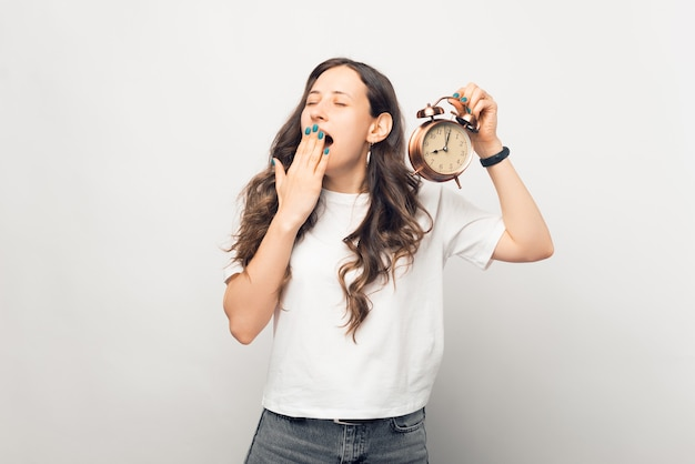 Young woman yawns while holding an alarm clock over white background.