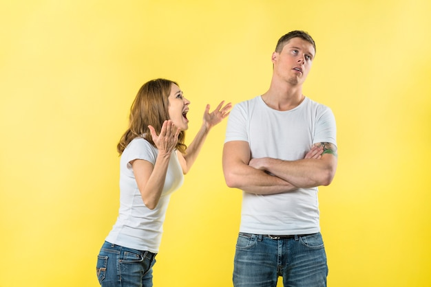 Young woman yelling on her boyfriend against yellow backdrop