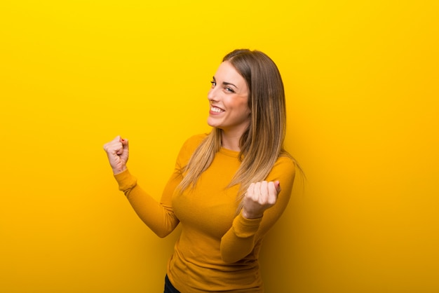 Young woman on yellow background celebrating a victory