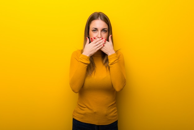 Young woman on yellow background covering mouth with hands for saying something inappropriate