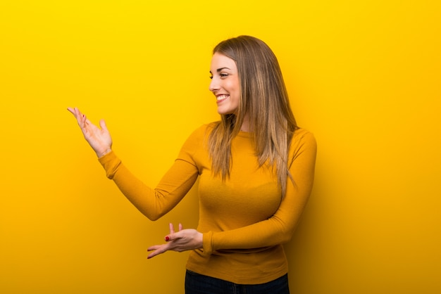 Young woman on yellow background extending hands to the side for inviting to come