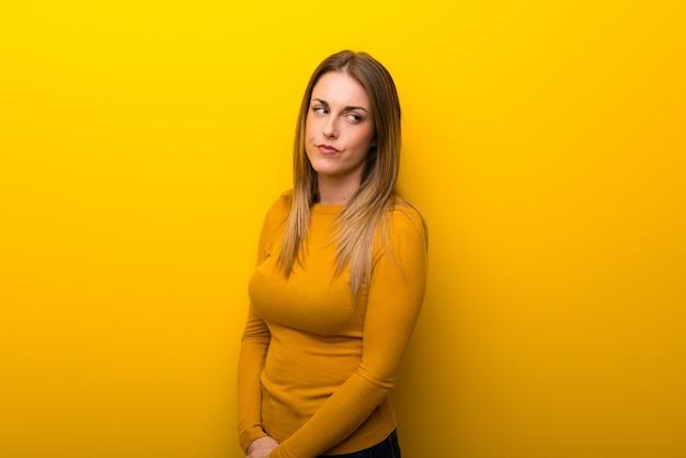Young woman on yellow background feeling upset