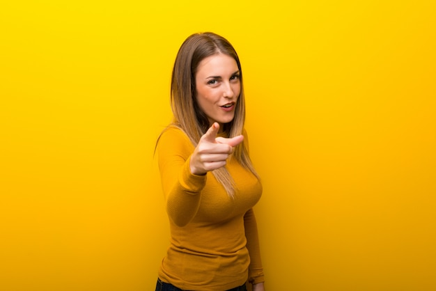 Young woman on yellow background frustrated by a bad situation and pointing to the front