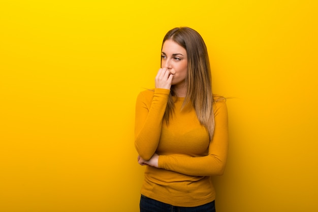 Young woman on yellow background having doubts