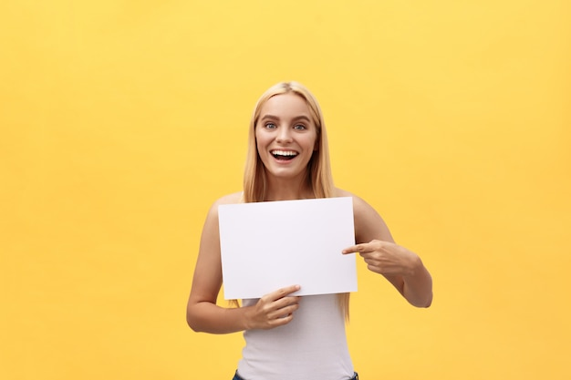 Young woman over yellow background holding blank paper sheet with surprise expression pointing finger copy space.