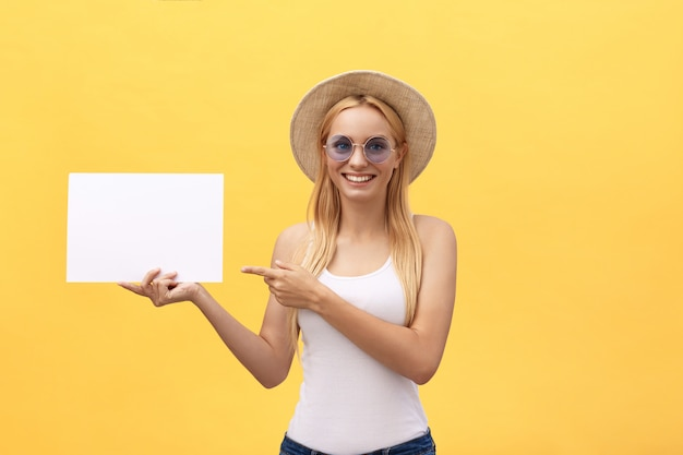 Young woman over yellow background holding blank paper sheet
