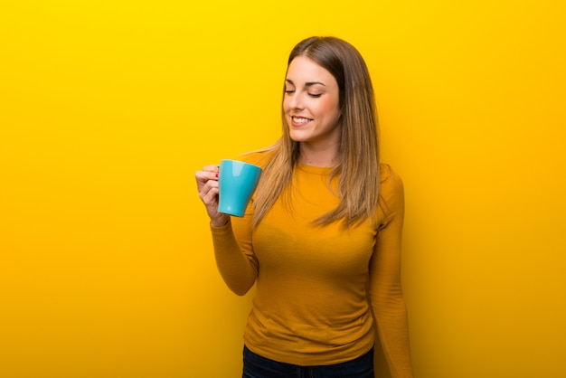 Young woman on yellow background holding a hot cup of coffee
