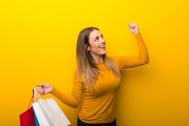 Young woman on yellow background holding a lot of shopping bags in victory position