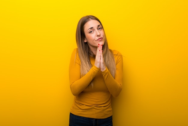 Young woman on yellow background keeps palm together. person asks for something