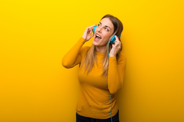 Young woman on yellow background listening to music with headphones