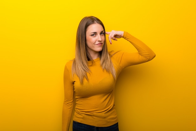 Young woman on yellow background making the gesture of madness putting finger on the head