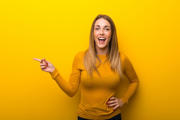 Young woman on yellow background pointing finger to the side and presenting a product
