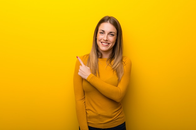 Young woman on yellow background pointing to the side to present a product