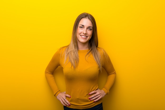 Young woman on yellow background posing with arms at hip and laughing looking to the front