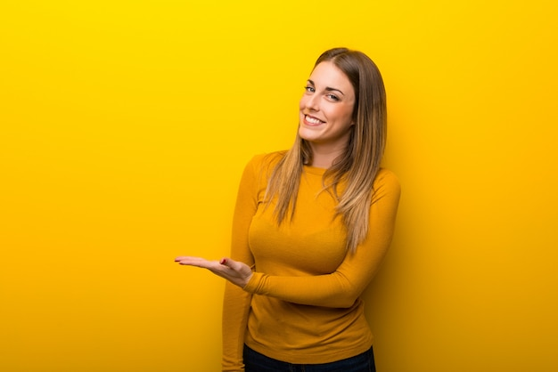 Young woman on yellow background presenting an idea while looking smiling towards