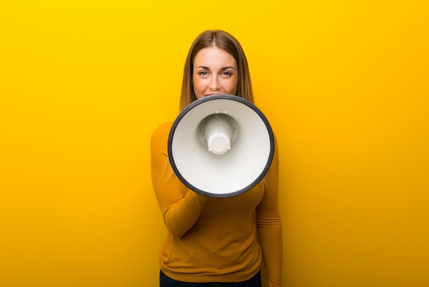 Young woman on yellow background shouting through a megaphone to announce something