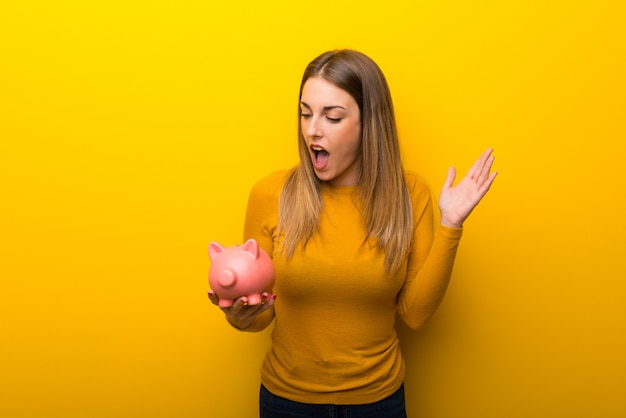 Young woman on yellow background surprised while holding a piggybank