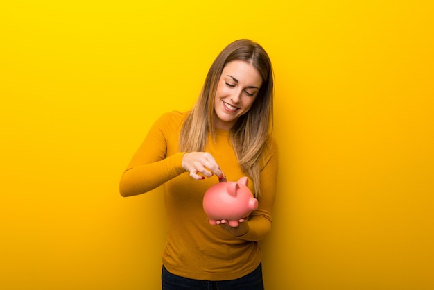 Young woman on yellow background taking a piggy bank and happy because it is full