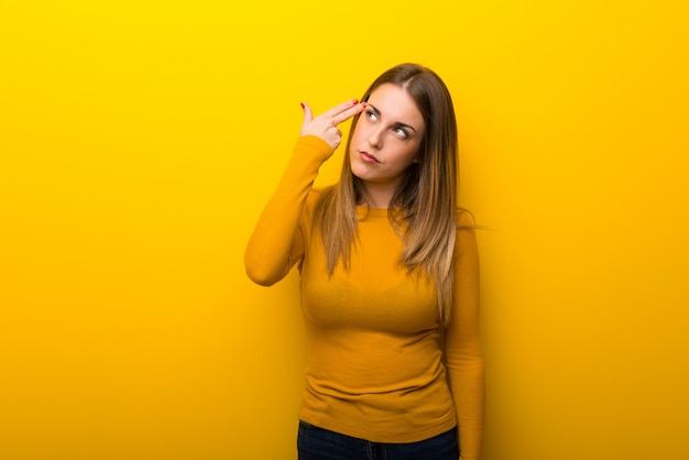 Young woman on yellow background with problems making suicide gesture