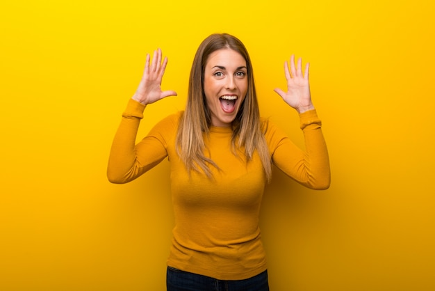 Young woman on yellow background with surprise and shocked facial expression