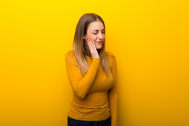Young woman on yellow background with toothache