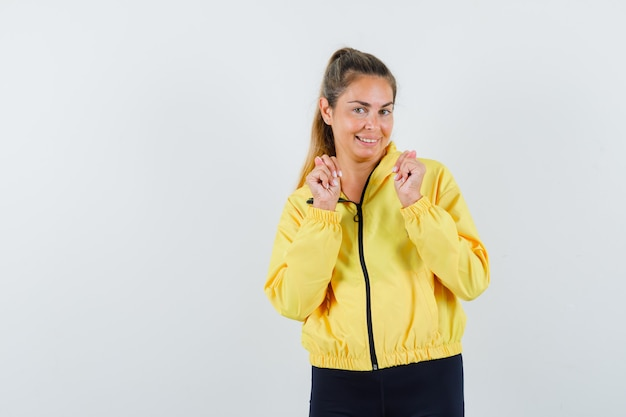 Giovane donna in bomber giallo e pantaloni neri che mostra il gesto del vincitore e che sembra carino