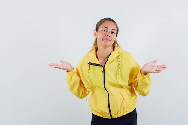 Giovane donna in bomber giallo e pantaloni neri che allunga le mani in modo interrogativo e sembra perplessa