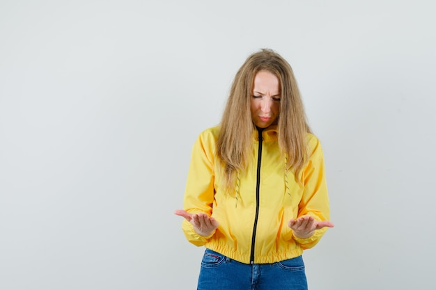 Young woman in yellow bomber jacket and blue jean looking at hands and looking lugubrious, front view.