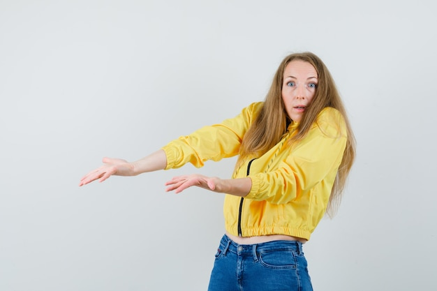 Young woman in yellow bomber jacket and blue jean pointing left with both index fingers and looking surprised , front view.