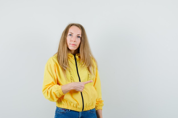 Young woman in yellow bomber jacket and blue jean pointing right and looking serious , front view.