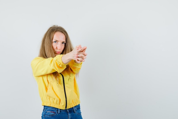Young woman in yellow bomber jacket and blue jean showing gun gesture and looking optimistic , front view.